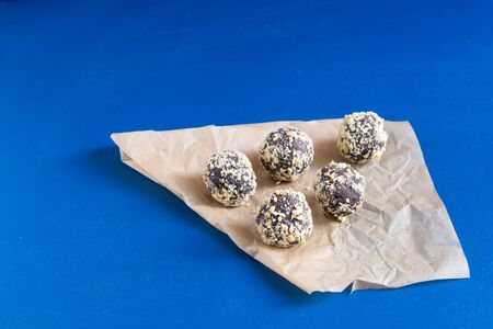 Several energy balls in wrapping paper on a blue table. Healthy homemade dessert for Breakfast will fill you with energy Фото со стока