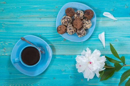 A Cup of black coffee and energy balls on a blue wooden table. White peony flower Фото со стока
