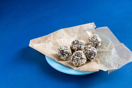 Five homemade energy balls in wrapping paper on a blue table. Healthy homemade chocolate dessert for Breakfast will fill you with energy . Nut sprinkles