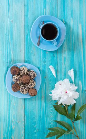 A Cup of coffee, a white peony flower, and energy balls on a plate. Healthy homemade chocolate dessert for Breakfast will fill you with energy . Sprinkle of nuts and cocoa