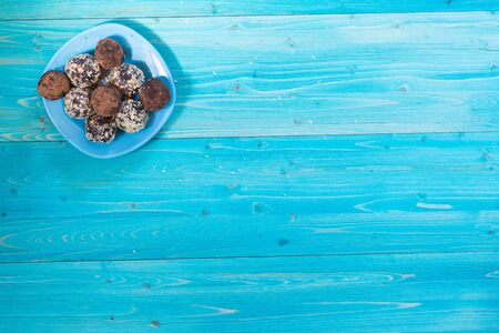 Energy balls in a plate on a blue table. Healthy homemade chocolate dessert for Breakfast will fill you with energy . Sprinkle of nuts and cocoa. Copy space