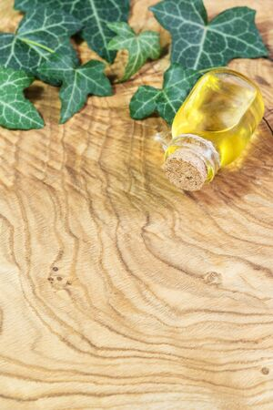 A bottle of vegetable oil on a wooden table. Omega-3-essential polyunsaturated fatty acids. Flaxseed oil in a bottle. Green leaves of ivy Hedera. Copy space