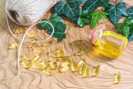 Transparent gelatinous capsules of fish oil were scattered on the wooden background near the oil bottle. Omega-3-essential polyunsaturated fatty acids. The neck of the bottle is tied with a hemp rope
