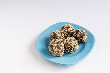 Five homemade energy balls on a blue plate. Healthy homemade chocolate dessert for Breakfast will fill you with energy . Nut sprinkles Фото со стока