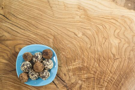 A portion of homemade energy balls in a blue plate on a textured wooden table. Delicious and healthy dessert. Lifestyle. The view from the top. Copy space