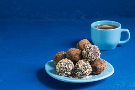 A portion of homemade energy balls and a Cup of tea with lemon on the blue table. Delicious and healthy dessert. Lifestyle. Copy space Фото со стока