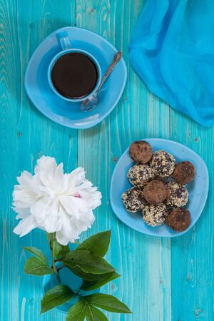 A portion of homemade energy balls and a Cup of black coffee on a blue wooden table. Delicious and healthy dessert. Lifestyle. The view from the top Фото со стока