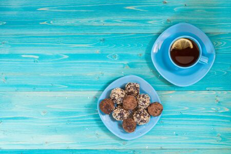 A portion of homemade energy balls and a Cup of tea with lemon on a blue wooden table. Delicious and healthy dessert. Breakfast. Lifestyle. The view from the top. Copy space