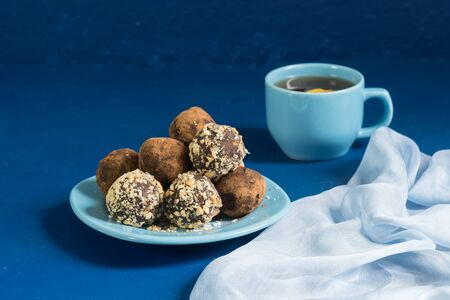 A portion of homemade energy balls and a Cup of tea with lemon on the blue table. Delicious and healthy dessert. Lifestyle. Close up