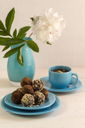 A portion of homemade energy balls and a Cup of tea on the table. Delicious and healthy dessert for Breakfast. Lifestyle