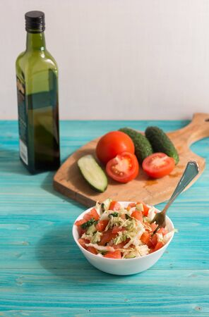 Vegetarian salad with fresh vegetables and olive oil on a blue wooden table. Light summer dinner. Lifestyle
