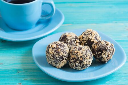 Five homemade energy balls on a plate and a Cup of coffee on a blue wooden table. Healthy homemade chocolate dessert for Breakfast will fill you with energy . Nut sprinkles Фото со стока