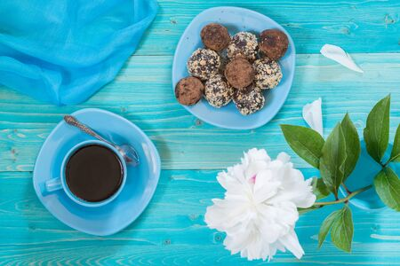 A portion of homemade energy balls and a Cup of black coffee on a blue wooden table. Delicious and healthy dessert. Breakfast. Lifestyle. The view from the top