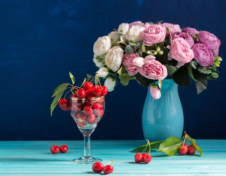 A glass glass with ripe red cherries stands on a blue table. In the background is a blue vase with peonies. Summer Lifestyle