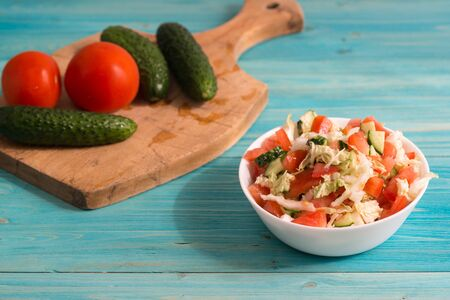 Vegetarian salad of fresh vegetables with olive oil in a white Cup on a blue wooden table. Tomatoes and cucumbers are on the cutting Board