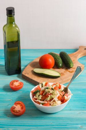 Cooking a vegetarian salad of fresh vegetables with olive oil on a blue wooden table. Light summer dinner. Lifestyle
