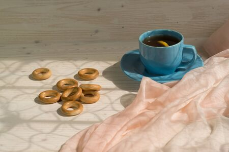 Morning tea with lemon and bagels on a wooden table. Sunlight from the window. Lifestyle Фото со стока