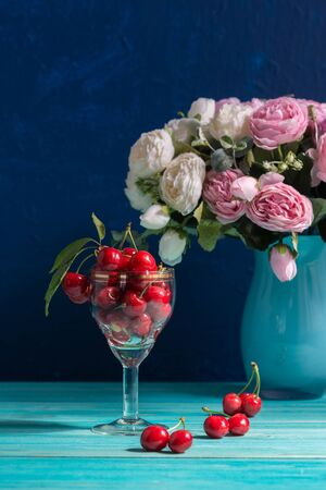 A glass glass with ripe red cherries stands on a blue table. In the background is a vase of peonies