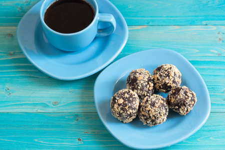 Five energy balls on a plate and a Cup of coffee on a blue wooden table. Healthy homemade chocolate dessert for Breakfast will fill you with energy. Nut sprinkles