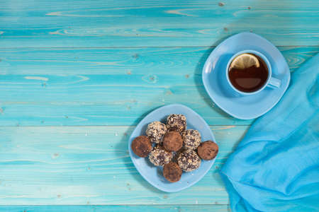 A portion of homemade energy balls and a Cup of tea with lemon on a blue wooden table. Delicious and healthy dessert. Lifestyle The view from the top. Copy space