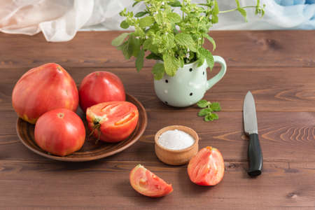 Large ripe juicy country pink tomatoes and a salt shaker on a wooden table. In the mug - a bunch of Melissa