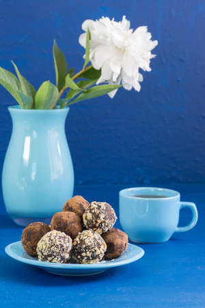 A portion of homemade energy balls and a Cup of tea on a blue background. Delicious and healthy dessert for Breakfast. Lifestyle