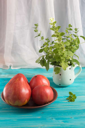 Large ripe sugar country pink tomatoes on a blue wooden table. In the mug - a bunch of Melissa