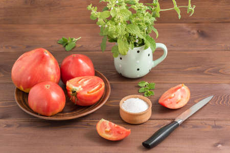 Large ripe juicy country pink tomatoes, a salt shaker with salt and a knife on a wooden table. In the mug - a bunch of Melissa