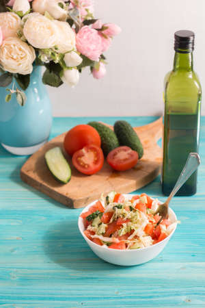 Vegetarian salad with fresh vegetables and olive oil on a blue wooden table. A bouquet of flowers in the background. Light summer dinner. Lifestyle