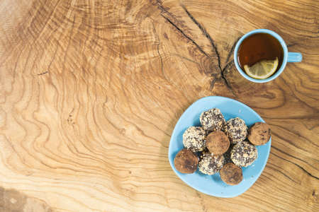 A portion of homemade energy balls in a blue plate and a Cup of tea with lemon on a textured wooden table. Delicious and healthy dessert. Lifestyle The view from the top. Copy space Фото со стока