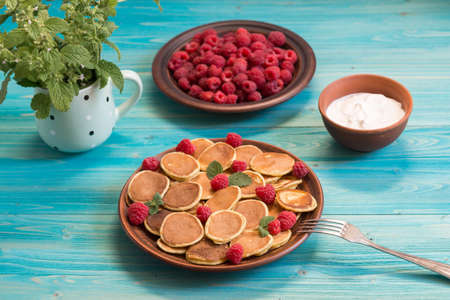 Pancake cereals and red ripe fresh raspberries in a brown plate on a blue wooden table. Delicious summer breakfast