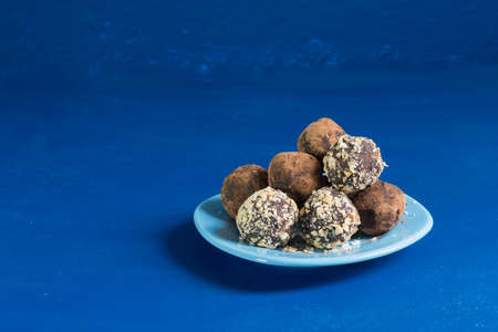 A portion of home energy balls on a blue background. Delicious and healthy dessert. Lifestyle Close up. Copy space Фото со стока