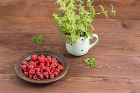 Juicy red ripe raspberries in a clay plate on a wooden table. In the mug is a bouquet of flowering Melissa. Summer Фото со стока