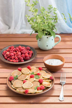 Pancake cereals and red ripe fresh raspberries in a brown plate. A bunch of Melissa in a mug on a dark wooden table near the window. Delicious summer breakfast