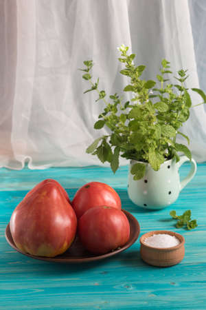 Large ripe sweet country pink tomatoes on a blue wooden table. In the mug - a bunch of Melissa Фото со стока