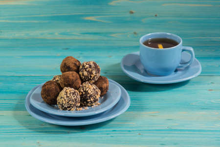 A portion of homemade energy balls and a Cup of tea on a blue wooden table. Delicious and healthy dessert for Breakfast. Lifestyle. Diet Фото со стока