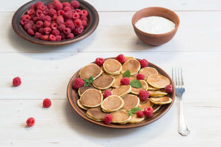 Pancake cereals with yogurt and ripe fresh raspberries in a brown plate on a white wooden table. Delicious summer breakfast
