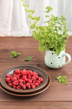 Red fresh raspberries on brown rustic wood background. Bowl with natural ripe organic berries on wooden table. Vertical Фото со стока