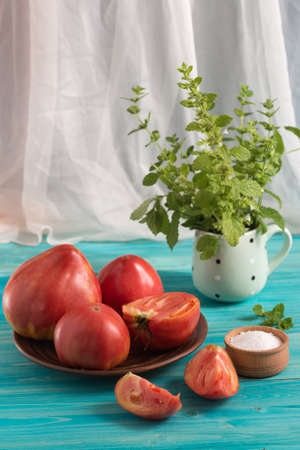 Large ripe sweet country pink tomatoes and a salt shaker on a blue wooden table. In the mug - a bunch of Melissa