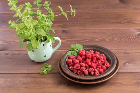 Red ripe fresh raspberries in a brown plate and a bunch of Melissa in a mug on a dark wooden table. Summer
