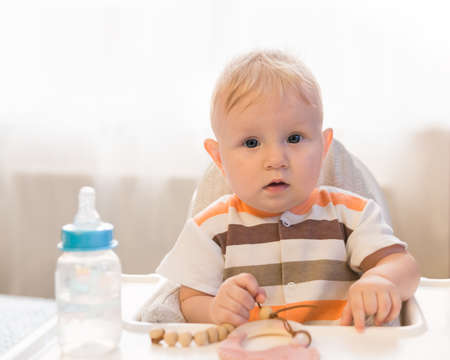 A small surprised blue-eyed child sits at a table and looks at the camera. On the table is a bottle with a pacifier and water. Amazement Reklamní fotografie
