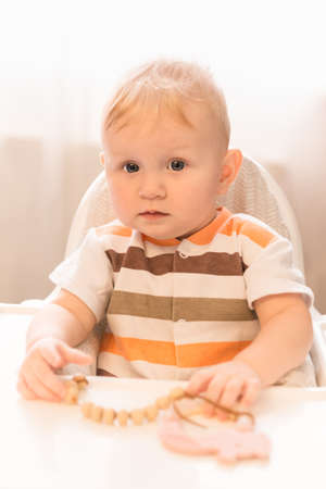 A small, serious, blue-eyed child sits at a table and looks at the camera. There is a toy on the table. Attention and alertness