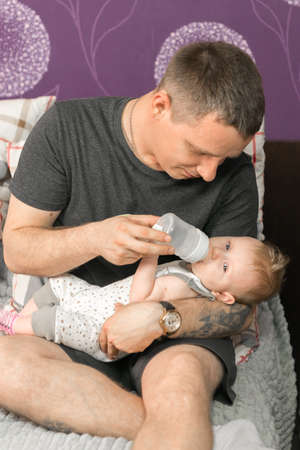 A father feeds a baby daughter formula from a bottle. Daily care of the child. Food Reklamní fotografie