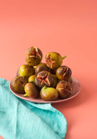 A lot of figs are on a pink plate next to a turquoise linen plate. Ripe fruit. Vertical