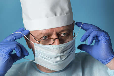 A doctor in medical clothing: a cap, gloves, dressing gown and glasses puts on or removes a protective mask. Close-up