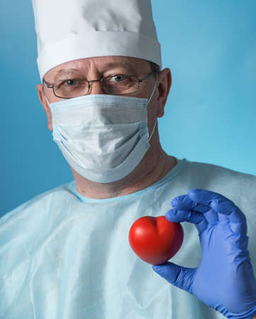 Portrait of a middle-aged serious experienced cardiologist surgeon in medical clothing: cap, gloves, dressing gown and mask, glasses. In the hands of the heart. Close-up view of the camera