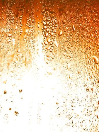 gaseosas: Cerveza, las gotas de l�quido de condensaci�n sobre un fondo de vidrio Foto de archivo