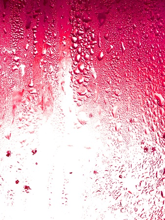 Granadine, fruit soda drops condensation on glass texture background photo