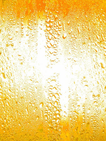 Yellow wet texture of a glass with little water drops on its surface  photo