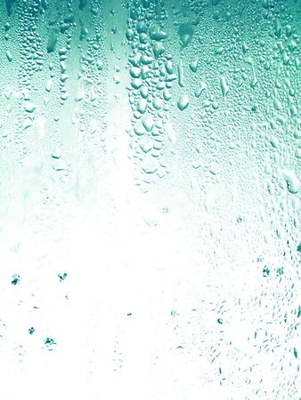 rains: Light aqua texture with drops of rain on a glass